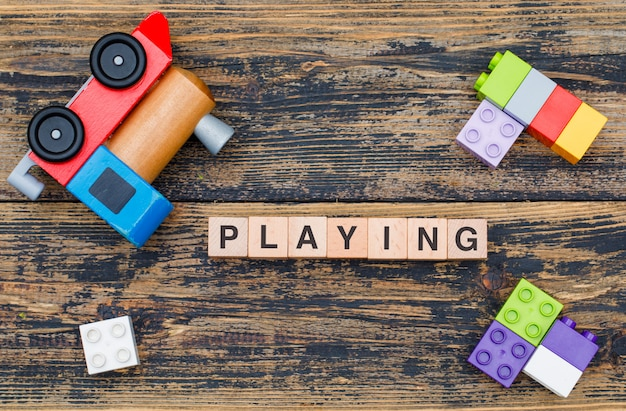 Playing toys concept with wooden cubes, kid toys on wooden background flat lay.