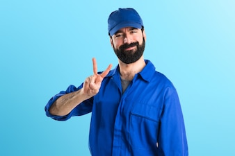 Plumber doing victory gesture on colorful background