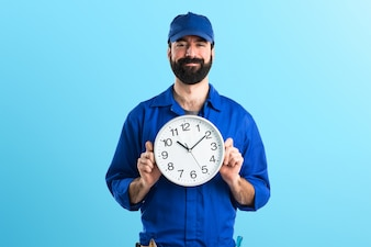 Plumber holding clock on colorful background