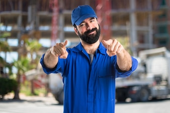 Plumber pointing to the front on unfocused background