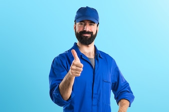 Plumber with thumb up on colorful background