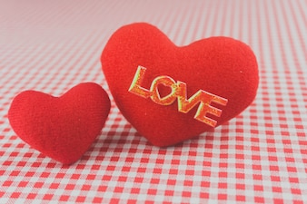 Plush hearts on a checkered tablecloth with the word  love