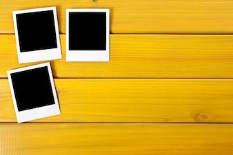Polaroid photo prints on a wood desk or table
