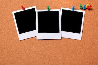 Polaroid photos pinned to a cork board