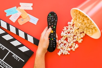 Popcorn, clapperboard and hand holding remote control