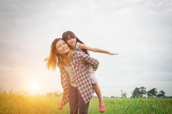 ポートレートママと娘は家族の時間を楽しんで、屋外で遊んで。