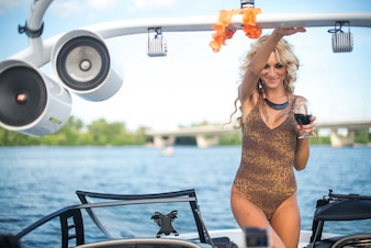 Portrait of a beautiful girl on a yacht with wine