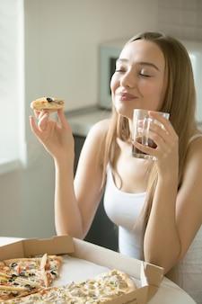 Портрет молодой женщины с пиццей в руке