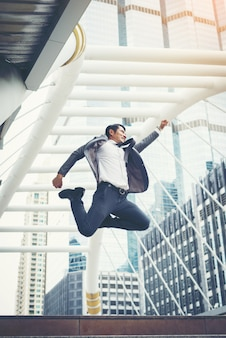 Portrait of Attractive businessman celebrates by jumping raises his fist overhead outdoor.