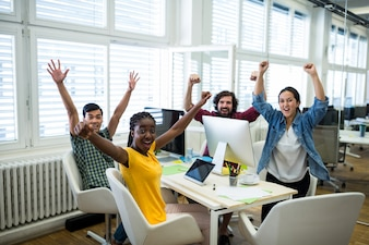 Portrait of business executives raising arms