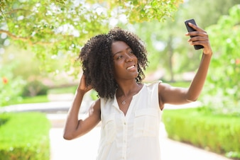 Portrait of cheerful woman taking selfie in park