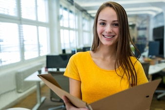 Portrait of female business executive holding a file