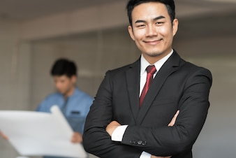 Portrait of handsome confident young businessman smiling