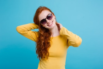 Portrait of happy ginger red hair girl with freckles smiling looking at camera. Pastel blue background. Copy Space.
