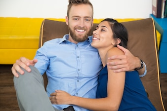 Portrait of happy young couple resting on couch