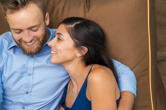 Portrait of happy young couple resting on sofa