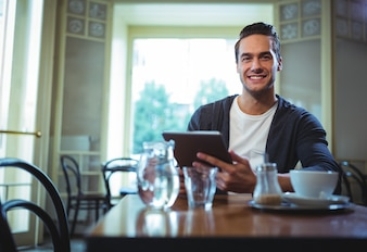 Portrait of man using digital tablet in café