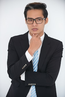 Portrait of serious young businessman thinking