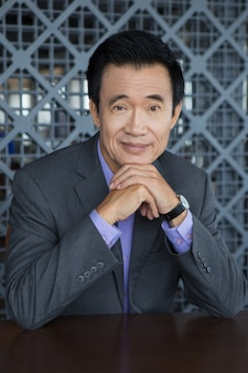 Portrait of Smiling Asian Man with Hands on Chin