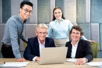 Portrait of successful team at laptop in office