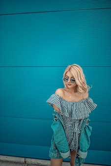 Portrait of Trendy Hipster Girl Standing at the blue turquoise wall Background. Urban Fashion Concept. Copy Space.