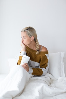 Portrait of upset young woman drinking tea in bed