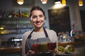 Portrait of waitress holding plate of juices