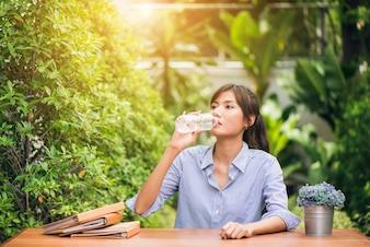 夏の緑の公園で青いTシャツの飲み水を身に着けている若い美しい黒髪の女性の肖像画。