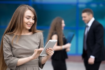 Portrait of young business woman looking at tablet screen