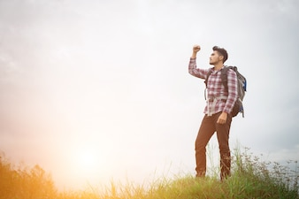 Portrait of young hipster man outdoor raising hands with backpac