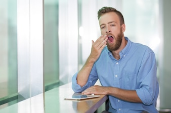 Portrait of young manager yawning in office