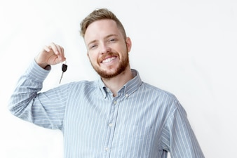 Positive face of young realtor holding car key
