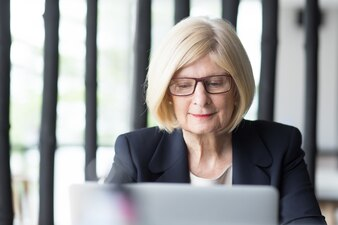 Positive senior businesswoman working on laptop