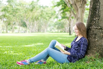 Positive student girl adoring reading book