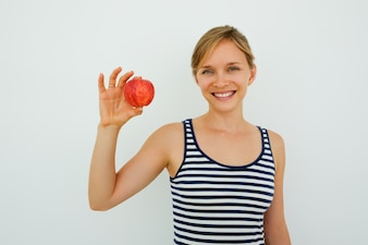 Positive woman with healthy teeth showing apple