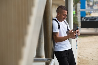 Positive young guy using smartphone outdoors