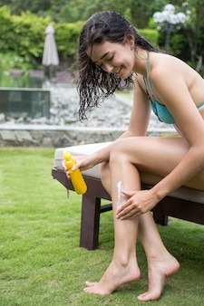Positive young woman applying sunscreen lotion