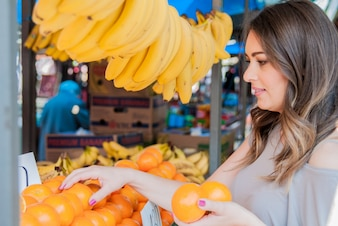 Positive young woman buying oranges on marketplace. woman choosing orange