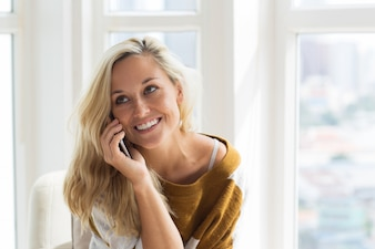 Positive young woman talking on mobile phone