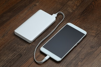 Powerbank and cellphone on wooden table