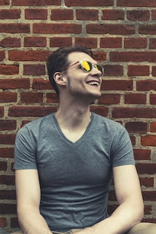 Pretty handsome young man hipster with sunglasses smiling laughing behind red brick wall. Toning.
