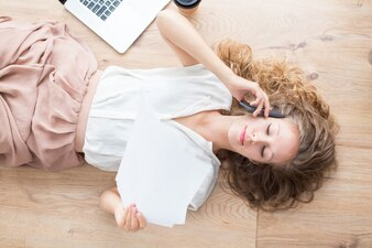 Pretty Lady Lying on Floor and Calling on Phone