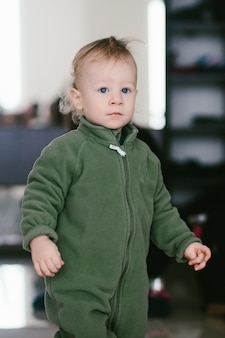 Pretty little boy in green jumpers stands before the mirror