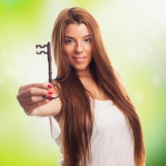 Pretty woman showing big key at camera