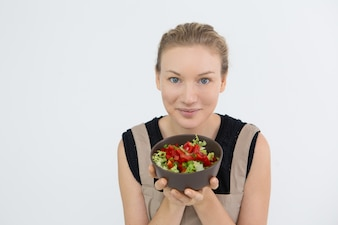 Pretty woman showing bowl with vegetable salad