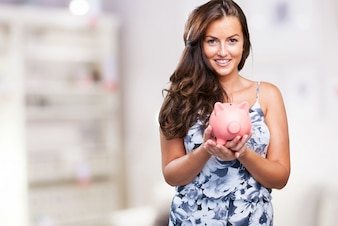 Pretty woman taking care of her piggy bank