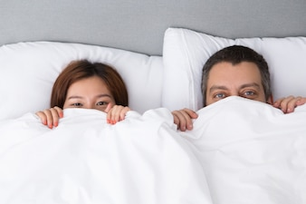 Pretty young couple hiding behind duvet