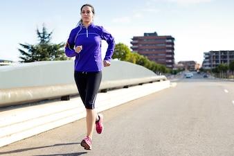 都市で走っている若い女性。