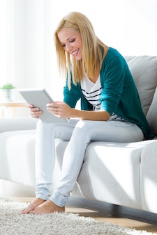Pretty young woman using her digital tablet at home.