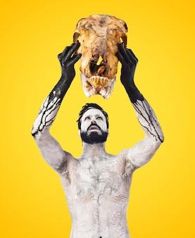 Primitive man offering veal skull on colorful background